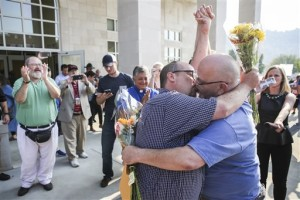 "Michael Long, left, and Timothy Long kiss outside the Rowan County Judicial Center, raising their fist clinched high in to the air after being the second couple to receive a marriage license. Gay couples walked out of the Kentucky courthouse with marriage licenses Friday, a day after the county's defiant clerk, Kim Davis, was taken to jail for refusing to license same-sex marriages, citing ""God's authority,"" Morehead, Ky, Sept. 4, 2015 