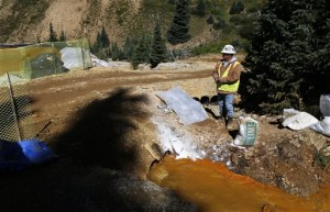 An Environmental Protection Agency contractor keeps a bag of lime on hand to correct the PH of mine wastewater flowing into a series of sediment retention ponds, part of danger mitigation in the aftermath of the blowout at the site of the Gold King Mine, outside Silverton, Colo. Federal officials say they have suspended cleanup work and investigations covering 10 mining sites in four states to guard against a repeat of last month's massive wastewater spill from an inactive Colorado gold mine. Details provided to The Associated Press show the order applies to three sites in California, four in Colorado, two in Montana and one in Missouri. Outside Silverton, Colo., Aug. 14, 2015 | AP File Photo by Brennan Linsley, St. George News