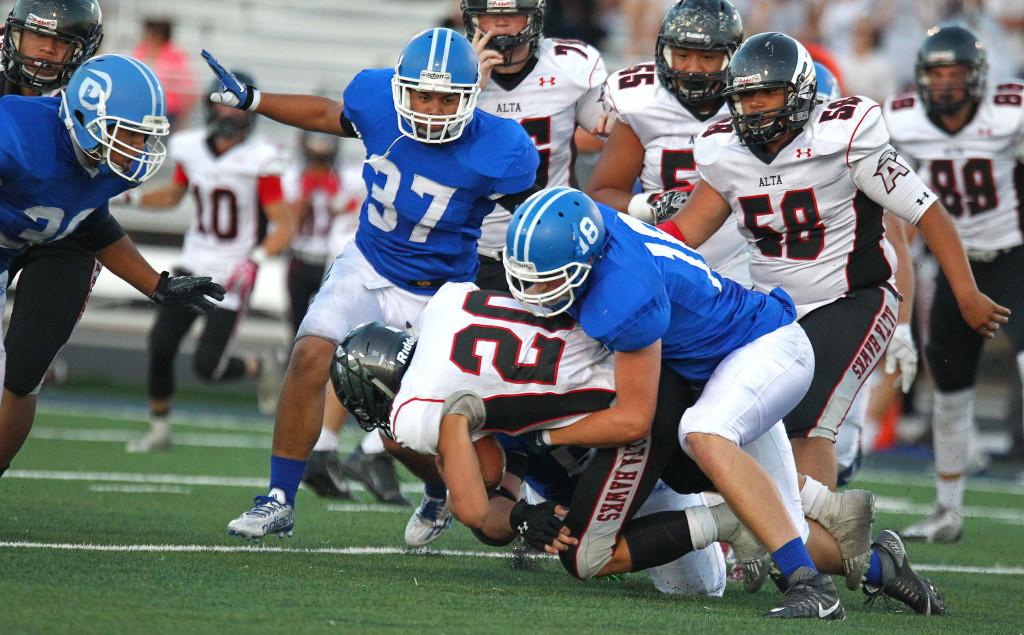 Tyson Fisher (18) takes down an Alta ball carrier, Dixie vs. Alta, Football, St. George, Utah, Sept. 4, 2015, | Photo by Robert Hoppie, ASPpix.com, St. George News