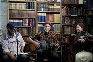 In this May 23, 2015, photo, Duncan Phillips, center, performs a song by songwriter Joe Hill along with Morgan Snow, left, and Kate MacLeod at Ken Sanders Rare Books in Salt Lake City. The event raised funds for a Joe Hill memorial concert planned for September in Sugar House Park. Hill was executed in Utah on Nov. 19, 1915, after being convicted of a murder many people believe he did not commit, Salt Lake City, Utah, May 23, 2015 | AP Photo by Jeremy Harmon, The Salt Lake Tribune, JOWHILL.SLTRIB.COM, St. George News