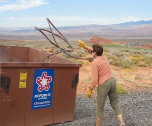 Joan Hayes throws garbage into a dumpster provided by BLM, as part of the Desert RATS public lands cleanup effort. Hurricane, Utah, Sept. 26, 2015 | Photo courtesy Desert RATS, exclusive to St. George News