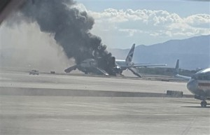 In this photo, taken from the view of a plane window, smoke billows out from an airplane that caught fire at McCarran International Airport. An engine on the British Airways plane caught fire before takeoff, forcing passengers to escape on emergency slides. Las Vegas, Nevada, Sept. 8, 2015 | AP Photo by Eric Hays, St. George News