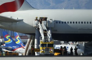 Firefighters enter a plane that caught fire at McCarran International Airport. An engine on the British Airways plane caught fire before takeoff, forcing passengers to escape on emergency slides, Las Vegas, Nevada, Sept. 8, 2015 | AP Photo/John Locher, St. George News
