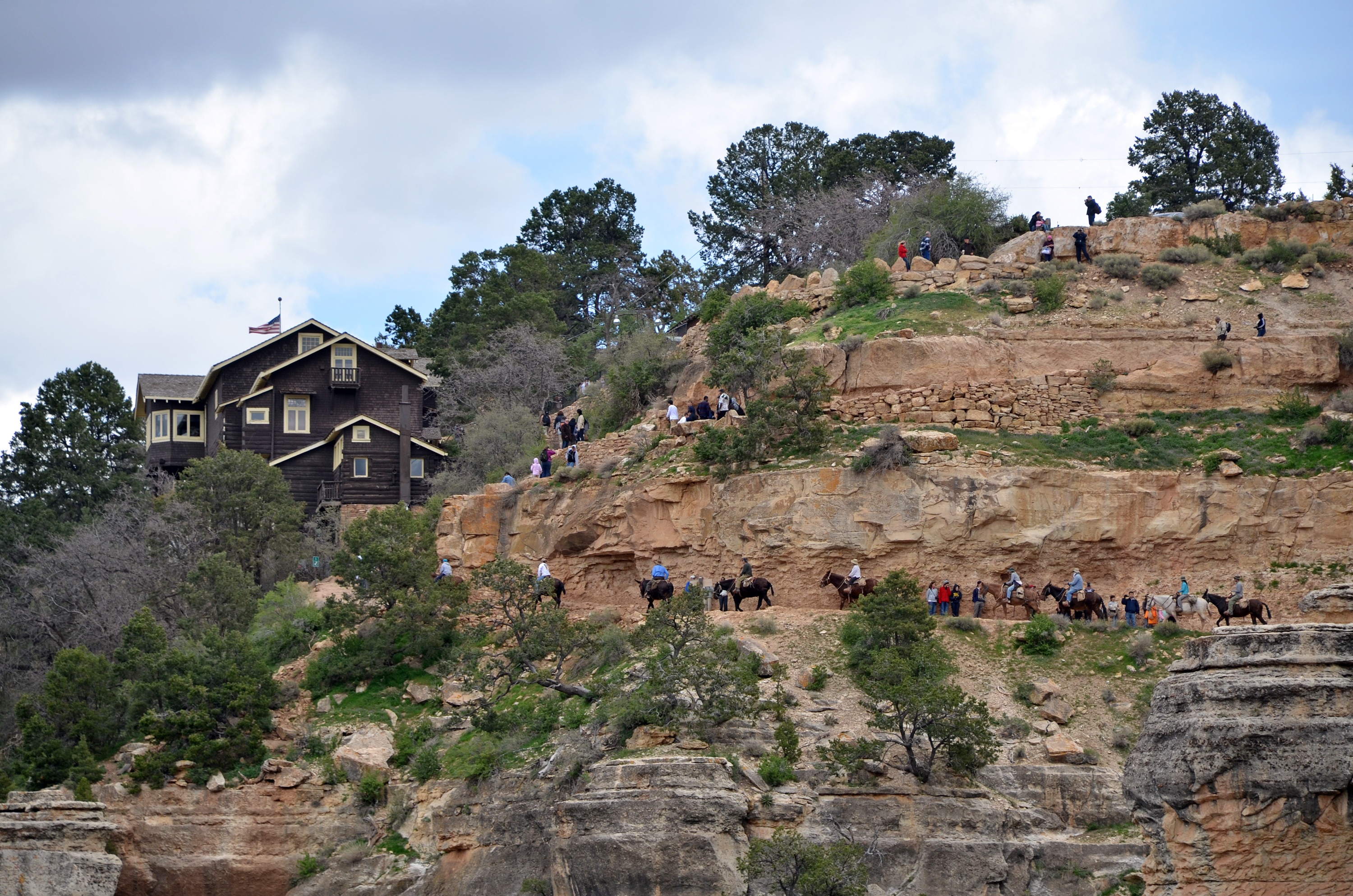 Hikers and Mule Riders reaching the top of the Bright Angel Trail on the South Rim. Kolb Studio (left) is part of Grand Canyon National Park's Historic District: South Rim. Photographers, Ellsworth L. Kolb and Emery C. Kolb played an important role in the early development of visitor services to the Grand Canyon. Ellsworth and Emery came to the Canyon in 1902. Ellsworth worked as a bellman in the Bright Angel Hotel. The brothers eventually bought a photographic studio in Williams, Arizona and brought the equipment to the Grand Canyon. Their business started out photographing parties going down the Bright Angel Trail. Because water supplies were limited on the rim of the Canyon, they would photograph the mule passengers then run 4 1/2 miles to Indian Garden where they had set up a photographic lab. Water was available here for processing the film. Then they returned to the rim of the Canyon with the processed pictures ready for the mule passengers on their return. Kolb Studio was constructed on this site from 1904 through 1926. It was a 2 1/2 story structure with the upper level on the rim of the Canyon. This building saw 23 years of expansion and alterations that brought it to its present day appearance. Grand Canyon National Park, 2011 | NPS Photo by Michael Quinn, St. George News