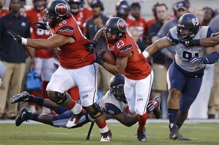 Utah running back Devontae Booker (23) tries to get away Utah State defender during the first half of an NCAA college football game Friday, Sept. 11, 2015, in Salt Lake City. (AP Photo/Rick Bowmer)