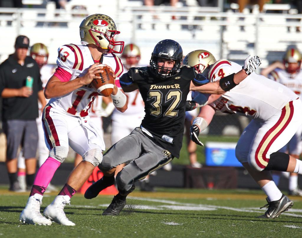 Zak Fuchs (32) puts pressure on Logan quarterback Hunter Horsley, Desert Hills vs. Logan, Football, St. George, Utah, Oct. 14, 2015, | Photo by Robert Hoppie, ASPpix.com, St. George News