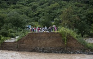 People stand at the edge of a collapsed bridge, overlooking the Ameca River in Cofradia, some 200 km northwest of Guadalajara, Mexico. Hurricane Patricia made landfall Friday on a sparsely populated stretch of Mexico's Pacific coast as a Category 5 storm, avoiding direct hits on the resort city of Puerto Vallarta and major port city of Manzanillo as it weakened to tropical storm force while dumping torrential rains that authorities warned could cause deadly floods and mudslides, Guadalajara, Mexico, Saturday, Oct. 24, 2015 | AP Photo/Eduardo Verdugo, St. George News