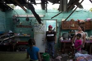 Josefina Magana Ruiz, center, surveys her home damaged by Hurricane Patricia, in La Fortuna, Mexico. Hurricane winds tore off much of the roof of the two-room home where seven people live, soaking mattresses and destroying belongings. Record-breaking Patricia pushed rapidly inland over mountainous western Mexico early Saturday, weakening to tropical storm force while dumping torrential rains that authorities warned could cause deadly floods and mudslides, La Fortuna, Mexico, Oct. 24, 2015 | AP Photo/Rebecca Blackwell, St. George News