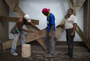"""Men nail boards across the shutters of a waterfront business, as residents prepare for the arrival of Hurricane Patricia in Puerto Vallarta, Mexico. Patricia barreled toward southwestern Mexico Friday as a monster Category 5 storm, the strongest ever in the Western Hemisphere. Locals and tourists were either hunkering down or trying to make last-minute escapes ahead of what forecasters called a """"potentially catastrophic landfall"""" later in the day, Puerto Vallarta, Mexico, Oct. 23, 2015   AP Photo/Rebecca Blackwell, St. George News"""