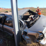 A passenger car came to rest against a highway sign after being forced off the road Wednesday morning, Washington, Utah, Oct. 7, 2015 | Photo by Ric Wayman, St. George News