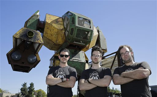 MegaBots founders from left, Brinkley Warren, Matt Oehrlein and Gui Cavalcanti stand below their 15-foot tall, piloted Mk.II robot at the Pioneer Summit in Redwood City, Calif. Let the giant robot wars begin. A team of American engineers challenged a group in Japan to a battle for robot supremacy, and the Japanese said bring it on. So Oakland-based MegaBots has launched a Kickstarter campaign to raise money to turn the Mk.II, into a real fighting machine, ready for hand-to-hand combat, Oct. 9, 2015 | AP Photo by Eric Risberg, St. George News