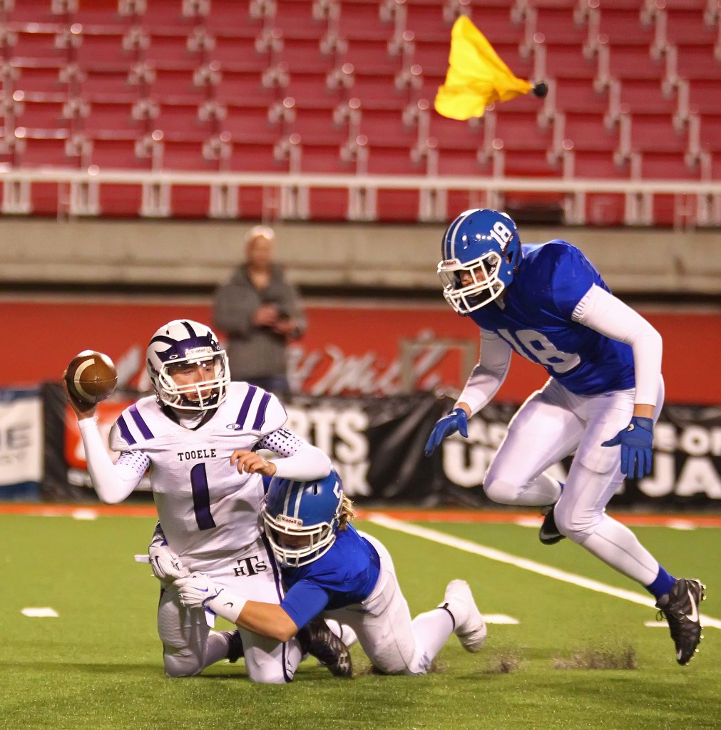 Dixie's  Cutler Thomas (5) sacks the Tooele quarterback as a penalty flag flies, Dixie vs. Tooele, 3AA Football Semifinals, Salt Lake City, Utah, Nov. 13th, 2015, | Photo by Robert Hoppie, ASPpix.com, St. George News
