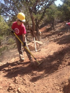 A volunteer from the Southern Utah University Intergovernmental Internship Cooperative rakes away debris on the new Iron Hills Trail System, Cedar City, Utah, 2015 | Photo courtesy of Dave Jacobson, St. George News
