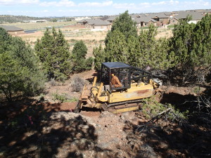 International Mountain Bike Association Trail Solutions employee Joey Klein clears a trail with the Utah State Parks Department trail dozer that was donated for the new Iron Hills Trail System, Cedar City, Utah, 2015 | Photo courtesy of Dave Jacobson, St. George News
