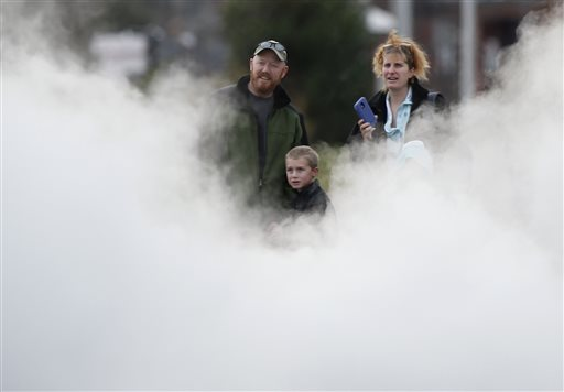 A family watches as steam shoots out from the locomotive as the Polar Express starts a journey on the Maine Narrow Gauge Railroad.