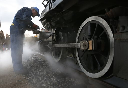 Engineer Joe Monty oils the moving parts of a steam locomotive used by the Maine Narrow Gauge Railroad for its annual runs of the Polar Express.
