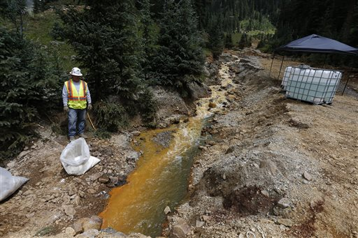 An Environmental Protection Agency contractor keeps a bag of lime on hand to correct the PH of mine wastewater flowing into a series of sediment retention ponds, part of danger mitigation in the aftermath of the blowout at the site of the Gold King Mine, outside Silverton, Colorado, Aug. 12, 2015 | AP Photo by Brennan Linsley, St. George News