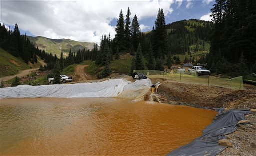 Water flows through a series of sediment retention ponds built to reduce heavy metal and chemical contaminants from the Gold King Mine wastewater accident, in the spillway about 1/4 mile downstream from the mine, outside Silverton, Colorado, Aug. 12, 2015 | AP Photo by Brennan Linsley, St. George News
