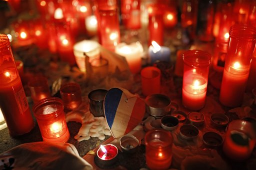 A wooden heart with the colors of the French flag rests among candles placed by people outside the French embassy in Madrid, Spain, Nov. 16, 2015 | AP Photo by Francisco Seco, St. George News