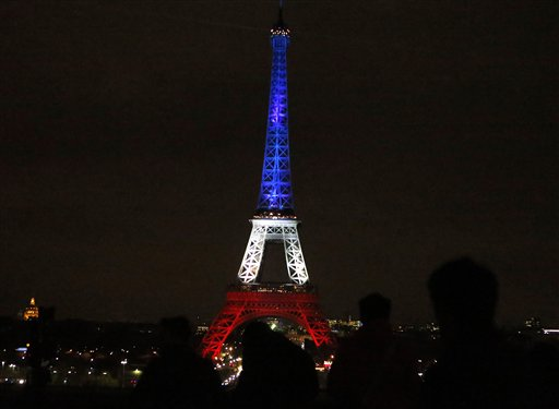People watch the Eiffel Tower illuminated in the French national colors red, white and blue in honor of the victims of the terror attacks last Friday in Paris, France, Nov. 16, 2015 | AP Photo by Frank Augstein, St. George News