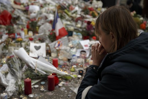 A woman prays as she pays her respect in front of a floral tribute near the Bataclan concert hall after Friday's terror attacks in Paris, France, Nov. 16, 2015 | AP Photo by Daniel Ochoa de Olza, St. George News