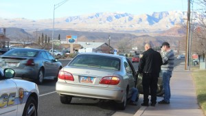 St. George Police Officer speaking with the driver and passenger of an Infiniti I30 involved in an accident on Sunset Blvd in St. George, Utah on December 28, 2015 | Photo by Don Gilman, St. George News