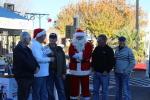"L-R: Owen Bouchard; Shane Dastrup; Retired Marine Gy. Sgt. Rick Massey, Toys for Tots Coordinator; Mike Thomas as Santa; John Heinz; performer Deonne Mendenhall; Car Guys Care's Toys for Tots ""Show and Shine"" car show at Ricardo's Restaurant, St. George, Utah, Dec. 12, 2015