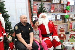 A police officer and a child pose with Santa at the annual Shop with a Cop event, Cedar City, Utah, Dec. 12, 2015   Photo by Emily Hammer, Cedar City News