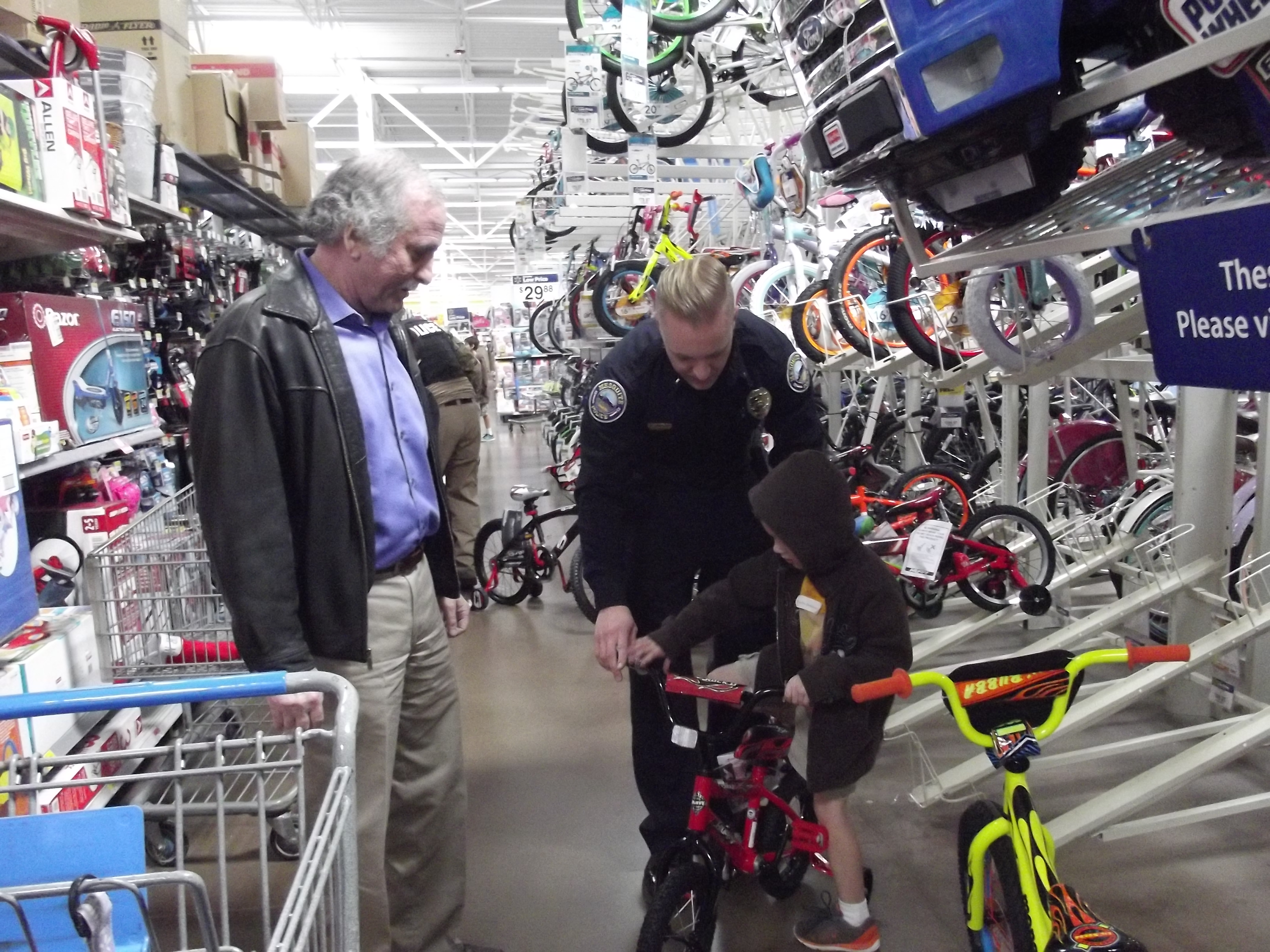 Lieutenant MaQuade Chesley and help a child pick out a bike at the Shop with a Cop event, Mesquite, Nevada, date unspecified | Photo courtesy of the Mesquite Police Department, St. George News