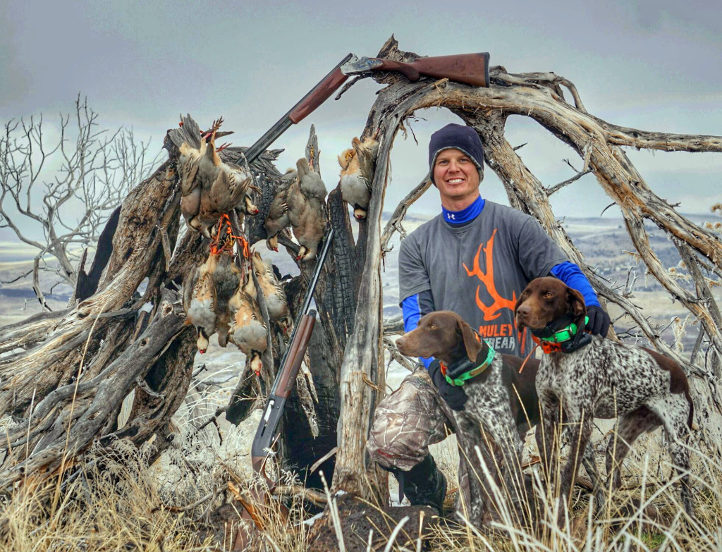 A hunter poses with his dogs and the chukars he caught, location and date unspecified | Photo courtesy of Clint Wirick, Utah Chukar and Wildlife Foundation, St. George News