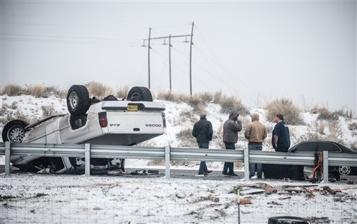 People stand by after a rollover accident along Interstate 25 northbound just south of Albuquerque, New Mexico, Dec. 26, 2015 | Roberto E. Rosales, The Albuquerque Journal via AP, St. George News