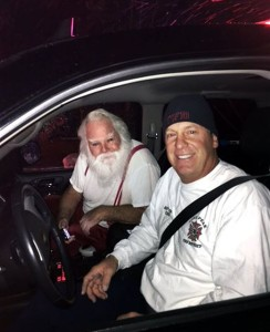 Lone Peak Fire District Battalion Chief Joseph McRae, right gives a ride to Orem, Utah resident Steven Macey, a Santa-for-hire, a ride to a home to deliver presents after fire crews put out a fire in Macey's car. Firefighters called to the car fire in the Utah suburb got a big surprise early Christmas morning when they discovered the stranded driver turned out to be Santa Claus on the way to deliver presents. Alpine, Utah, Dec. 25, 2015 | Photo by Lt. Dustin Mitchell/Lone Peak Fire District via AP, St. George News