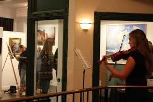 """Artist Aimee Bonham paints in the background during an Art on Main gallery stroll, St. George, Utah, November, 2015 