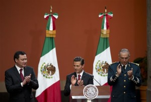 "Mexican President Enrique Pena Nieto, flanked by Interior Minister Miguel Angel Osorio Chong, left, and National Defense Secretary Slavador Cienfuegos Zepeda, applauds during a press conference following the capture of fugitive drug lord Joaquin ""El Chapo"" Guzman. Pena announced that Guzman had been recaptured six months after escaping from a maximum security prison, Mexico City, Mexico, Friday, Jan. 8, 2016. 