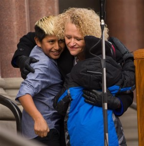Jackie Biskupski hugs her sons Jack Iverson and Archie Biskupski following her remarks during the swearing-in ceremony. Biskupski was sworn in as Salt Lake City's first openly gay mayor. Salt Lake City, Jan. 4, 2016   Photo courtesy of Scott G Winterton of The Deseret News via AP, St. George News