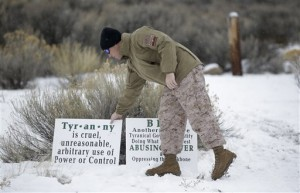 Jon Ritzheimer, of Arizona, a member of the group occupying the Malheur National Wildlife Refuge headquarters, adjust a sign. Law enforcement had yet to take any action Tuesday against the group numbering close to two dozen who are upset over federal land policy. Tuesday, Jan. 5, 2016, near Burns, Oregon, Jan. 5, 2015 | AP Photo/Rick Bowmer, St. George News