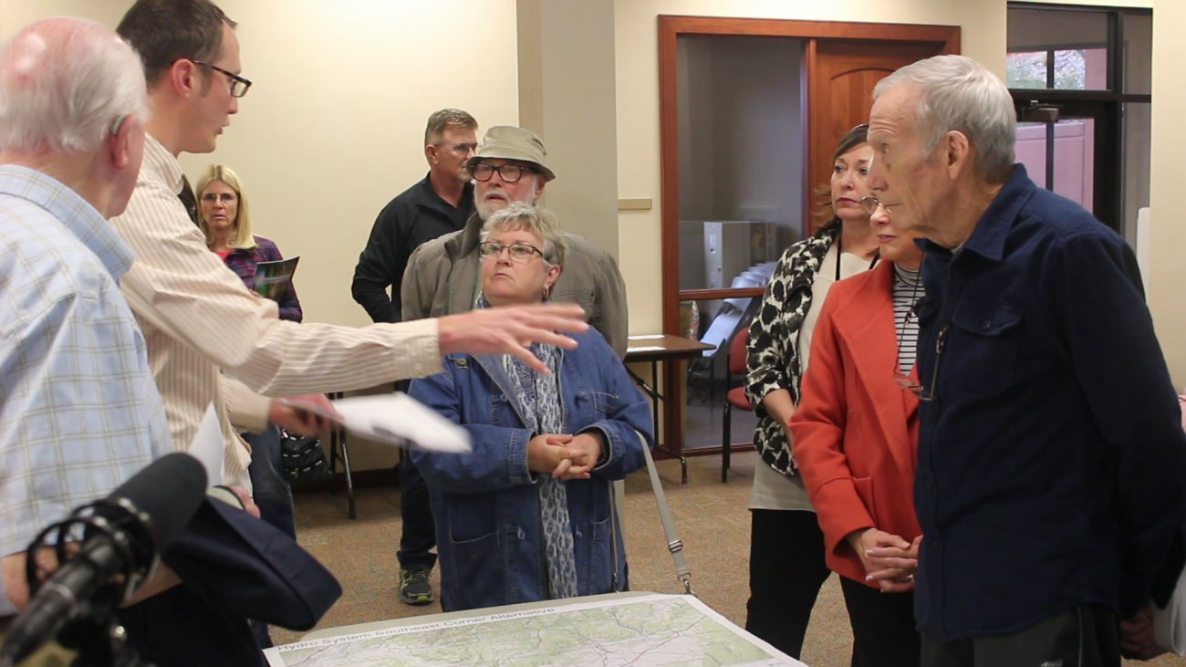 People listen to Joel Williams (second from left in light striped shirt), of the Utah Division of Water Resource, answering questions about the Lake Powell Pipeline project at an open house held at the Washington County Water Conservancy District Wednesday night. St. George, Utah, Jan. 16, 2016 | Photo by Mori Kessler, St. George News