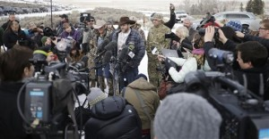 Ammon Bundy, center, one of the sons of Nevada rancher Cliven Bundy, speaks with reporters during a news conference at Malheur National Wildlife Refuge headquarters Monday, Jan. 4, 2016, near Burns, Ore. Bundy, who was involved in a 2014 standoff with the government over grazing rights, told reporters on Monday that two local ranchers who face long prison sentences for setting fire to land have been treated unfairly. The armed anti-government group took over the remote national wildlife refuge in Oregon as part of a decades-long fight over public lands in the West, Malheur National Wildlife Refuge, Oregon, Jan. 4, 2016 | AP Photo/Rick Bowmer, St. Goerge News