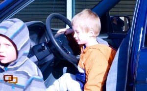Son of Aaron and Annie VanMeter takes a seat behind the wheel of a van big enough for all six members of their family, given to them Monday by the Wade Family Foundation at Dealer Collision Center, St. George, Utah, Feb. 1, 2016 | Photo by Julie Applegate, St. George News