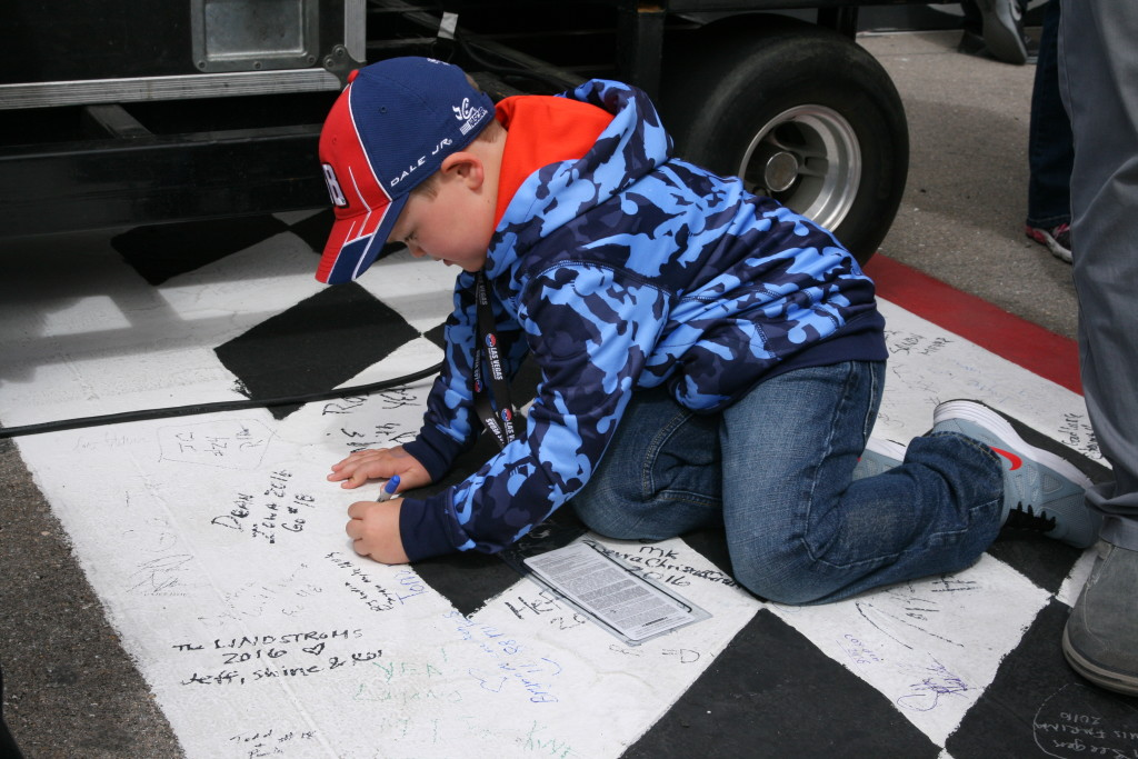 A young NASCAR fan puts his mark on the start/finish line at the Kobolt 400, Las Vegas, Nev., Mar. 6, 2016. | Photo by Rick Johnson, special to St. George News
