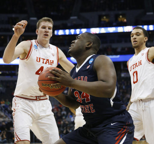 Fresno State center Terrell Carter II, front, goes up for a shot as Utah forwards Jakob Poeltl, back left, and Brekkott Chapman defend in the first half of a first-round men's college basketball game Thursday, March 17, 2016, in the NCAA Tournament in Denver. (AP Photo/Brennan Linsley)