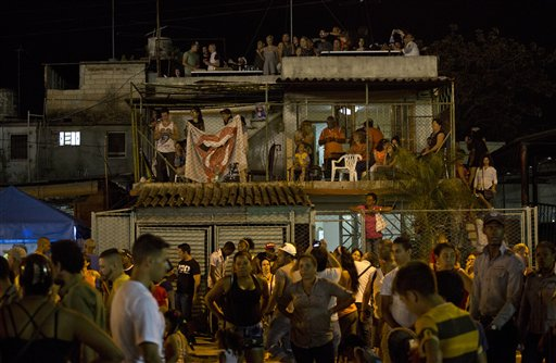 Fans watch the Rolling Stones concert from a neighboring house next to the venue, at the Ciudad Deportiva in Havana, Cuba, Friday. The Stones performed a free concert in Havana, becoming the most famous act to play Cuba since its 1959 revolution. Havana, Cuba, March 25, 2016 | AP Photo/Desmond Boylan