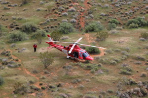 A Life Flight helicopter waits in a grassy spot a short distance from where a climber fell on a rappel from the Cougar Cliffs in St. George, Utah, Mar. 12, 2016 | Photo by Don Gilman, St. George News