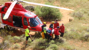 Rescuers carry an inured climber towards the waiting Life Flight helicopter at the base of the Cougar Cliffs in St. George, Utah, Mar. 12, 2016 | Photo by Don Gilman, St. George News