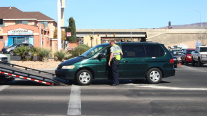 A Washington City police officer looks on as a Honda minivan is loaded onto a tow truck after a collision at the intersection of Green Springs Drive and Telegraph Street 1in Washington City, Utah, Mar. 19, 2016 | Photo by Don Gilman, St. George News