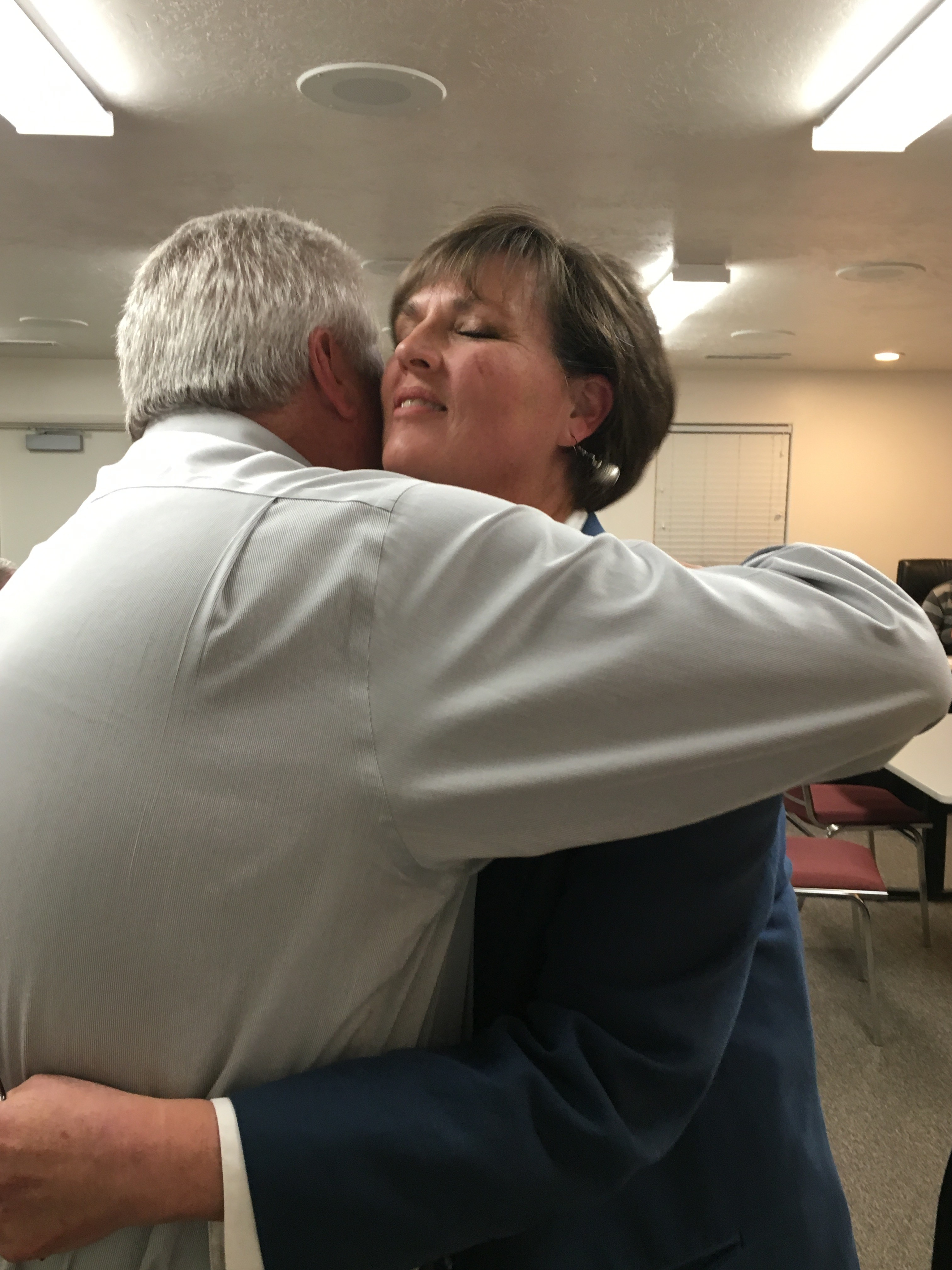 New Enoch City Councilwoman Jolene Lee hugs her husband after winning the coin toss Wednesday night in a tie between her and Scott Leel. Enoch City, Utah, March 2, 2016 | Photo by Tracie Sullivan, Cedar City News