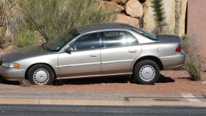 A gold Buick Century that left the road when the driver fell asleep at the wheel and crashed through a light pole in St. George, Mar. 2, 2016. | Photo by Don Gilman, St. George News.