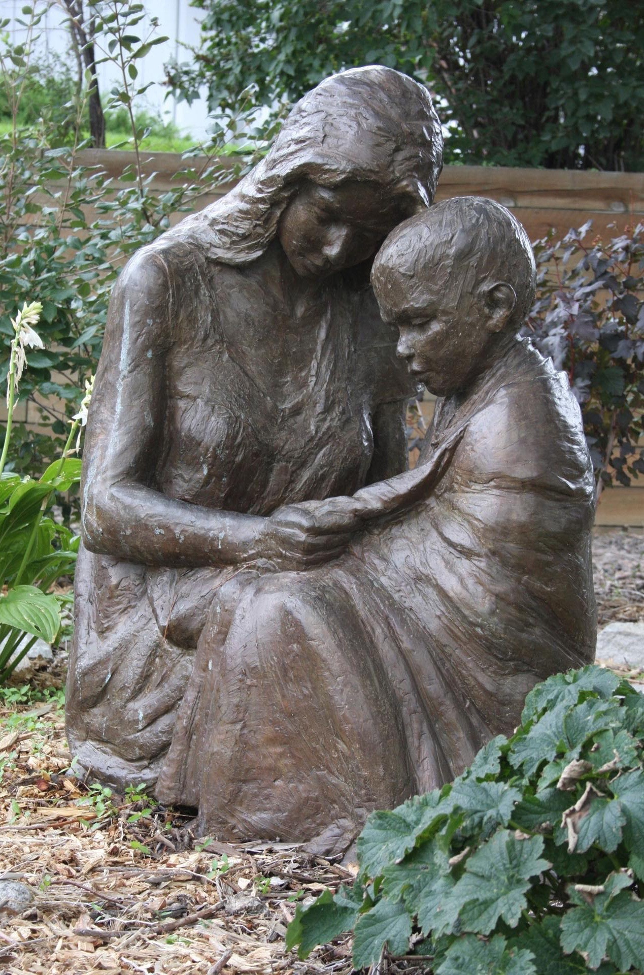 "Karen Crain's piece, to be installed by April 9, 2016, in the Outdoor Sculpture Exhibit by Art Around the Corner in St. George, is entitled ""Comforter."" A mother kneeling and holding her blanket-shrouded child represents the fleeting moments, the healing touches and the bond of tenderness. St. George, Utah 