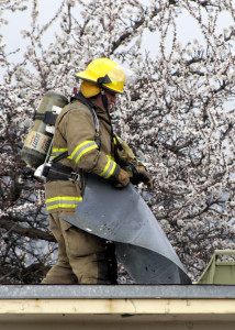 Firefighter Travis Topham tears apart the roof to access hot spots, 260 E. 400 North, Cedar City, Utah, March 22, 2016 | Photo by Carin Miller, St. George News