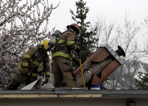 Battalion Chief Matt Gale and Firefighter Travis Topham tear apart the roof to access hot spots, 260 E. 400 North, Cedar City, Utah, March 22, 2016 | Photo by Carin Miller, St. George News